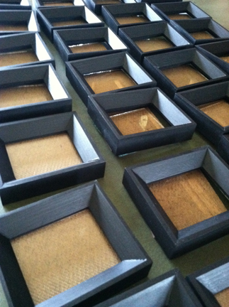 Painted frames are mated with backs and glass.